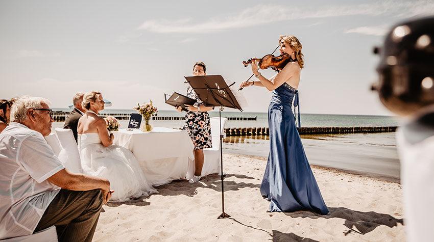 Eine Hochzeit am Strand, die mit Musik untermalt wird: Besser geht es nicht. © Fotostudio am Haff